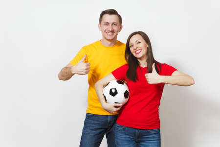 Fun smiling cheerful young couple, woman, man, football fans in yellow and red uniform cheer up support team holding soccer ball isolated on white background. Sport, family leisure, lifestyle concept