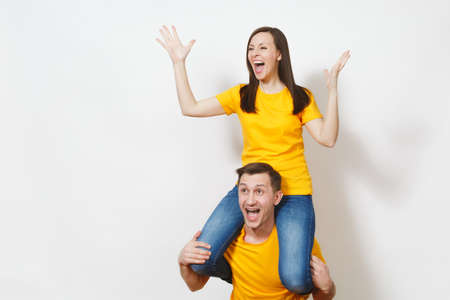 Fun inspired young couple, woman sit on man shoulders, fans in yellow cheering favorite team, expressive gesticulating hands isolated on white background. Sport, family leisure, lifestyle concept