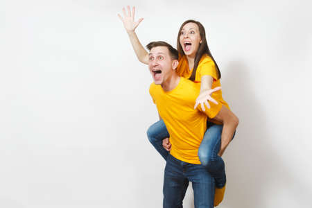 Fun inspired young couple, woman sit on man piggyback, fans in yellow cheering favorite team, expressive gesticulating hands isolated on white background. Sport, family leisure, lifestyle concept Imagens
