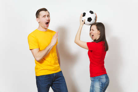 Fun crazy cheerful European young couple, woman, man, football fans in yellow red uniform hold play soccer ball isolated on white background. Sport, game football, family leisure, lifestyle concept Archivio Fotografico