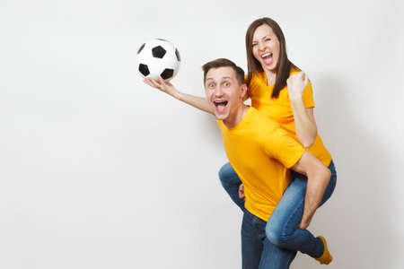 Inspired young couple, woman sit on man piggyback, fans with soccer ball cheering favorite football team expressive gesticulating hands isolated on white background. Family leisure, lifestyle concept
