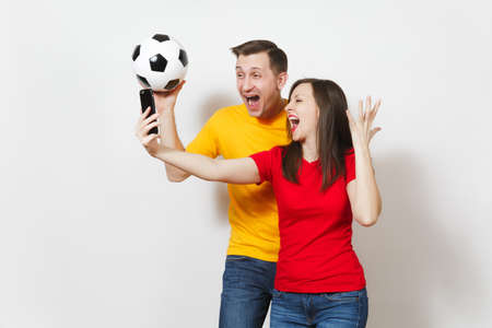 Fun crazy engaged young couple, man, woman doing selfie on mobile phone, football fans cheer up support team with soccer ball isolated on white background. Sport, family leisure, lifestyle concept Imagens