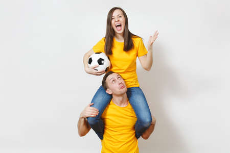 Inspired young couple, woman sit on man shoulders, fans with soccer ball cheering favorite football team expressive gesticulating hands isolated on white background. Family leisure, lifestyle concept