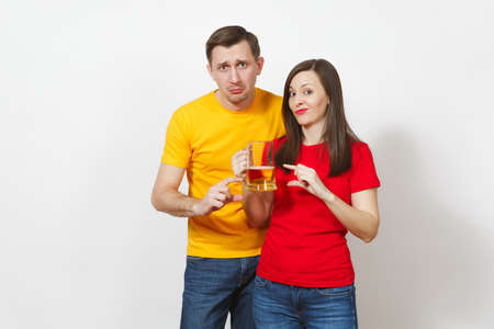 Sad upset crying young couple, woman, man, football fans in yellow red t-shirts with pint mug of little beer, show fingers ends isolated on white background. Sport, family leisure, lifestyle concept