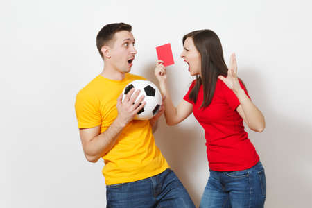 European angry aggressive young woman, football referee in red uniform show red soccer card, propose man player with soccer ball retire from field isolated on white background. Sport football concept Stock Photo