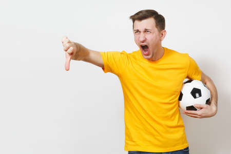 Inspired young European man, fan or player in yellow uniform hold soccer ball, cheer favorite football team, expressive gesticulate hands isolated on white background. Lifestyle concept. Copy space