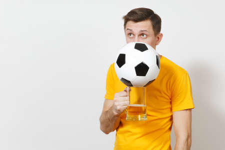 Young fun cheerful European man, fan or player in yellow uniform hide behind pint mug of beer, soccer ball cheer favorite football team isolated on white background. Sport, play, lifestyle concept