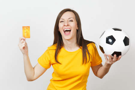 Beautiful European young cheerful woman, football fan or player in yellow uniform holding credit card soccer ball isolated on white background. Sport, play football game, excitement lifestyle concept Stock Photo