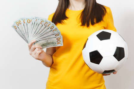 Close up cropped European young woman football fan or player in yellow uniform hold bundle cash dollars soccer ball isolated on white background. Sport play football game excitement lifestyle concept