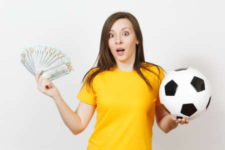 European young fun woman, football fan or player in yellow uniform holding bunch of money banknotes soccer ball isolated on white background. Sport, play football game, excitement lifestyle concept Stock Photo