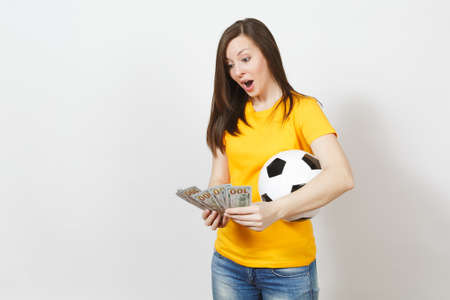European young cheerful woman, football fan or player in yellow uniform counting bundle cash dollars soccer ball isolated on white background. Sport, play football game, excitement lifestyle concept Stock Photo