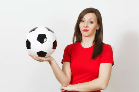 Pretty European young sad upset woman, football fan or player in red uniform holds soccer ball, worries about losing team isolated on white background. Sport, play football, lifestyle concept