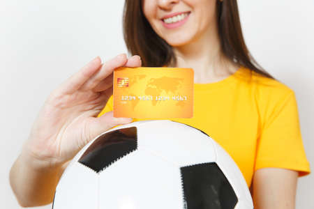 Close up cropped European young woman, football fan or player in yellow uniform holding credit card soccer ball isolated on white background. Sport, play football game, excitement lifestyle concept