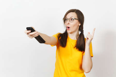 Irritated dissatisfied European young woman, football fan or player in yellow uniform hold TV remote, worries about losing team isolated on white background. Sport fan, healthy lifestyle concept