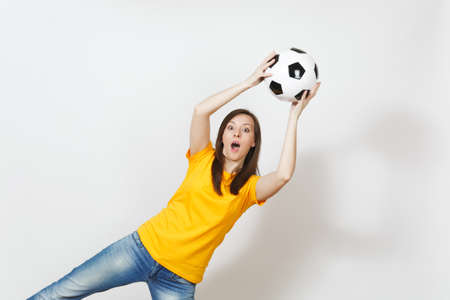 Beautiful European young goalkeeper woman, football fan or player in yellow uniform catching soccer ball in air isolated on white background. Sport, play football, health, healthy lifestyle concept 免版税图像