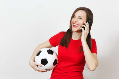 European young woman, two fun pony tails, football fan or player in red uniform hold soccer ball, talk on mobile phone isolated on white background. Sport play football, healthy lifestyle concept Stock Photo