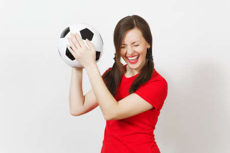 Overjoyed European young woman, two fun pony tails, football fan or player in red uniform holding classic soccer ball isolated on white background. Sport football health, healthy lifestyle concept
