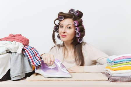 Young pretty housewife with curlers on hair in light clothes ironing family clothing on ironing board with iron. Woman isolated on white background. Housekeeping concept. Copy space for advertisement Stock Photo