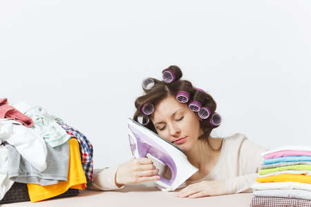 Tired housewife with curlers on hair in light clothes fell asleep on iron on ironing board with family clothing. Woman isolated on white background. Housekeeping concept. Copy space for advertisement Stock Photo