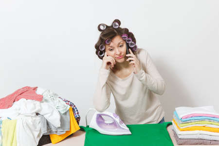 Distressed housewife in light clothes with curlers on hair talking on mobile phone, ironing family clothing on ironing board with iron. Woman isolated on white background Copy space for advertisement