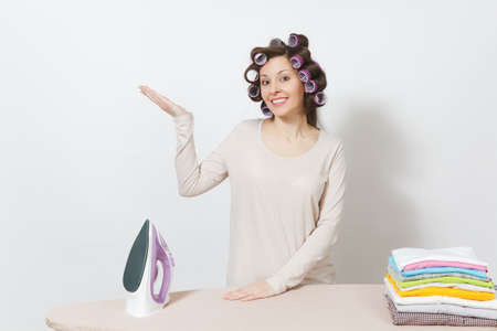 Housewife with curlers on hair in light clothes stand at ironing board with iron, family clothing . Woman point hand aside isolated on white background. Housekeeping concept. Copy space advertisement