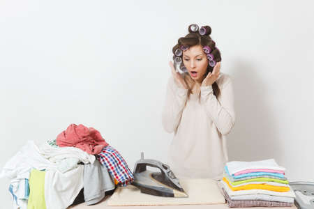 Distressed housewife with curlers on hair in light clothes ironing family clothing on ironing board with iron steam. Woman isolated on white background. Housekeeping concept. Copy space advertisement