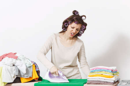 Distressed housewife with curlers on hair in light clothes ironing family clothing on ironing board with iron. Woman isolated on white background. Housekeeping concept. Copy space for advertisement Stock Photo