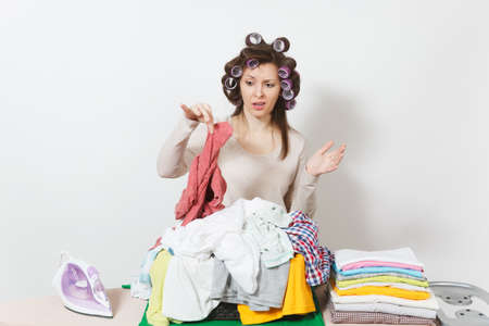 Distressed upset housewife with curlers on hair in light clothes with basket pile unshielded family clothing on ironing board with iron. Woman isolated on white background. Copy space advertisement