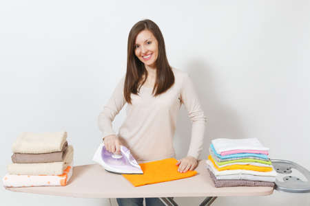 Young attractive housewife in light casual clothes ironing family clothing, towels on ironing board with iron. Woman isolated on white background. Housekeeping concept. Copy space for advertisement 免版税图像