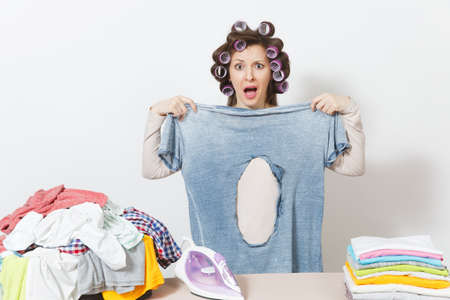 Shocked fun crazy housewife, curlers on hair in light clothes holding burned shirt with hole made by iron, standing at ironing board. Woman isolated on white background. Copy space for advertisement