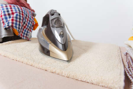 Close up steam iron, ironing colorful clothes, washed laundry, family clothing on ironing board isolated on white background. Housekeeping concept. Copy space for advertisement. With place for text