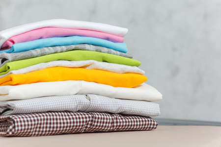 Close up pile of ironing colorful clothes, washed laundry, family clothing on ironing board isolated on white background. Housekeeping concept. Copy space for advertisement. With place for text Фото со стока