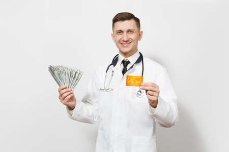 Smiling young doctor man isolated on white background. Male doctor in medical uniform, stethoscope holding bundle of dollars, banknotes cash money, credit card.