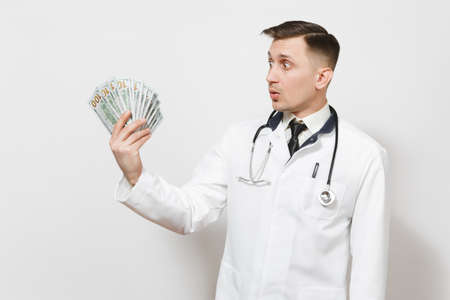 Shocked young doctor man isolated on white background. Male doctor in medical uniform, stethoscope looking on bundle of dollars, banknotes, cash money. Healthcare personnel, health, medicine concept