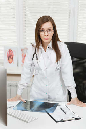 Young confident female doctor standing at desk, holding X-ray of lungs, fluorography, roentgen in light office in hospital. Woman in medical gown, stethoscope in consulting room. Stock Photo
