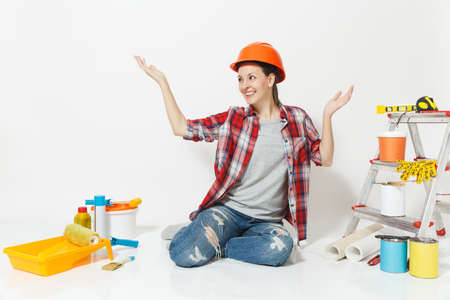 Woman in orange protective helmet sitting on floor with instruments for renovation apartment room isolated on white background. Wallpaper, accessories for gluing, painting tools. Repair home concept