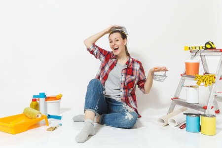 Woman holds metal grocery baskets for shopping, sits on floor with instruments for renovation apartment isolated on white background. Wallpaper, accessories, tools for painting. Repair home concept