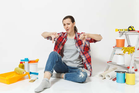 Confused annoyed tired shocked woman sitting on floor with instruments for renovation apartment isolated on white background. Wallpaper, accessories for gluing, painting tools. Concept of repair home