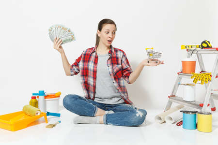 Woman holds bundle of cash money, supermarket grocery push cart for shopping. Instruments for renovation apartment isolated on white background Wallpaper accessories for gluing Concept of repair home Reklamní fotografie