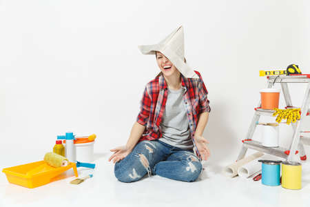 Happy fun woman in newspaper hat sitting on floor with instruments for renovation apartment room isolated on white background.