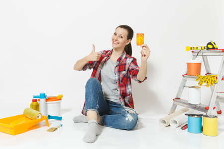 Cute woman holding credit card with money sitting on floor with instruments for renovation apartment isolated on white background.