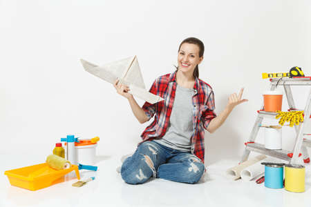 Woman in casual clothes sitting on floor with newspaper hat, instruments for renovation apartment isolated on white background. Wallpaper, accessories for gluing, painting tools. Repair home concept