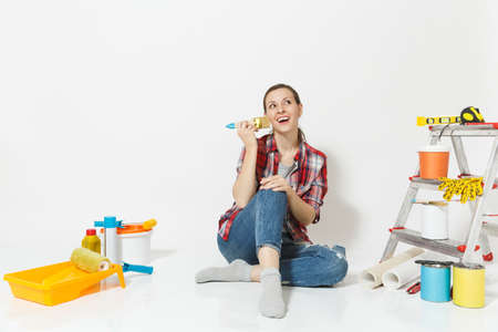 Pretty woman in casual clothes sitting on floor with brush, instruments for renovation apartment room isolated on white background. Wallpaper accessories for gluing painting tools Repair home concept