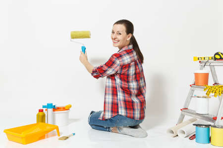 Pretty woman sitting on floor with paint roller, instruments for renovation apartment room isolated on white background.