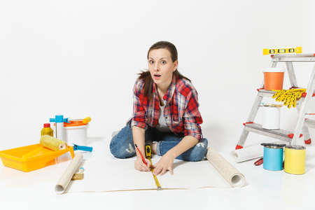 Woman sitting on floor with wallpaper rolls, measure tape, instruments for renovation apartment isolated on white background. Accessories for gluing, painting tools. Repair home concept. Copy space Reklamní fotografie