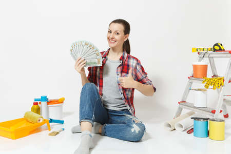 Woman holds bundle of dollars cash money, sits on floor with instruments for renovation apartment isolated on white background. Wallpaper accessories for gluing painting tools. Concept of repair home Reklamní fotografie