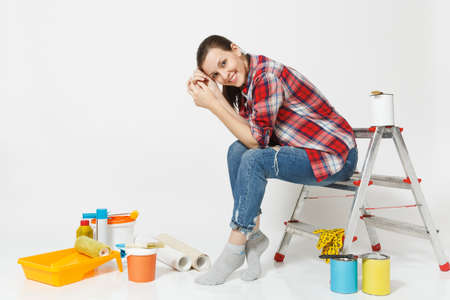 Pretty woman in casual clothes sitting on ladder with instruments for renovation apartment room isolated on white background. Wallpaper, accessories for gluing, painting tools. Repair home concept