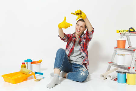 Fun pretty woman in casual clothes sitting on floor with yellow gloves, instruments for renovation apartment isolated on white background. Wallpaper, accessories painting tools. Repair home concept