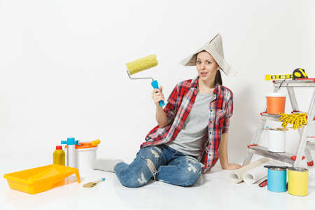 Cute woman in newspaper hat sitting on floor with paint roller, instruments for renovation apartment isolated on white background. Wallpaper accessories for gluing painting tools. Repair home concept