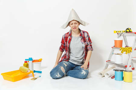 Crying sad woman in newspaper hat sitting on floor with instruments for renovation apartment room isolated on white background. Stock Photo